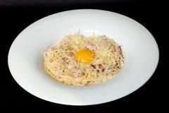 Cuisine italienne, poche d'oeufs, spaghetti, pâte de carbonate sur un fond noir photographie stock libre de droits