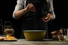 cuisine Le cuisinier fait cuire la pâte pour des pâtes, pizza, pain Arrose avec du sel Nourriture délicieuse, recettes, faisant c image stock