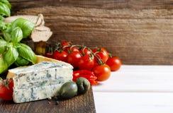 Cuisine méditerranéenne : fromage bleu, tomates, olives, plan de basilic Photo stock