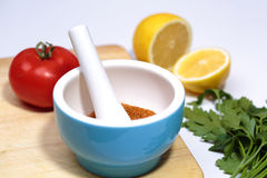 Cuisine. Mortar with herbs, sliced ​​lemon, tomato, greens. The process of cooking Stock Image