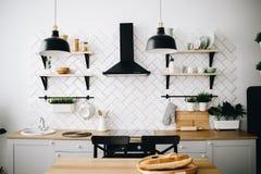 Cuisine scandinave moderne spacieuse de grenier avec les tuiles blanches et les appareils noirs Pi?ce lumineuse Int?rieur moderne photo libre de droits