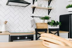 Cuisine scandinave moderne spacieuse de grenier avec les tuiles blanches et les appareils noirs Pi?ce lumineuse Int?rieur moderne images stock
