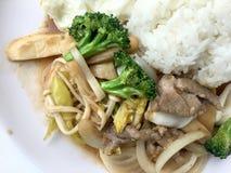 Cuisine thaïe Légumes colorés faits sauter à feu vif, oignon, brocoli, champignon avec de la viande dans le plat blanc avec du ri photographie stock