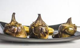 Cuisine traditionnelle : artichauts cuits dans le four avec le pétrole et le citron image stock