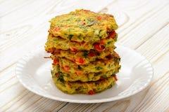Cuisine végétarienne - beignets végétaux (avec les pommes de terre, la carotte, la courgette, le paprika et le persil) photographie stock