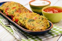 Cuisine végétarienne - beignets végétaux (avec les pommes de terre, la carotte, la courgette, le paprika et le persil) Image libre de droits