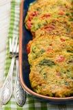 Cuisine végétarienne - beignets végétaux (avec les pommes de terre, la carotte, la courgette, le paprika et le persil) photo stock