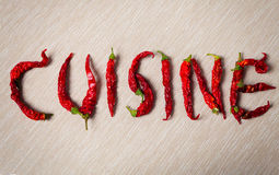 Cuisine. Word with dried red hot chili pepper Stock Image