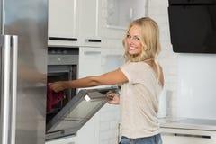 Cuisinière de fille avec le four avec le grand sourire Photo libre de droits