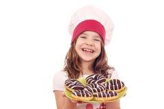 Cuisinière de petite fille avec des butées toriques de chocolat sucré Photographie stock