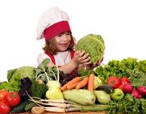 Cuisinière de petite fille avec des légumes Images stock