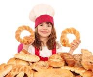 Cuisinière de petite fille avec des petits pains et des petits pains de pain Photographie stock libre de droits
