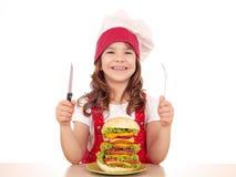 Cuisinière de petite fille avec le grand hamburger sur la table Image libre de droits