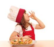 Cuisinière de petite fille avec le signe correct et saumons sur le plat Images stock