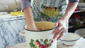 Cuisinière Kneads de femme la pâte dans une casserole sur la cuisine à la maison banque de vidéos