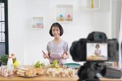 Cuisini?res de petite fille dans la cuisine ? la maison, avec l'enregistrement faisant la cam?ra visuelle de blogger photos stock