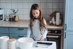 Cuisinières de petite fille dans la cuisine Images stock