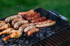 cuisinier à l'extérieur Saucisses et poulet sur le gril Photo stock