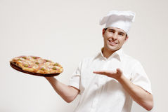 Cuisinier attirant heureux avec une pizza dans des mains Photographie stock