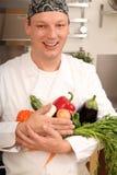 Cuisinier avec des légumes Photo stock