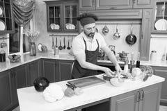Cuisinier barbu concentré faisant la salade végétale dans la cuisine photo stock