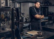 Cuisinier barbu dans l'uniforme noir se tenant avec les bras croisés dans la cuisine Photos stock
