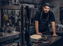 Cuisinier barbu dans le tablier et chapeau se penchant sur une table et regardant l'appareil-photo dans la cuisine Photographie stock