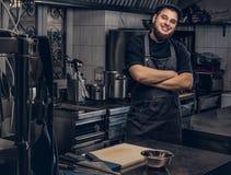 Cuisinier barbu de sourire dans l'uniforme noir se tenant avec les bras croisés dans la cuisine Image libre de droits