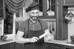 Cuisinier barbu positif coupant le poivre utilisant le couteau de cuisine images libres de droits