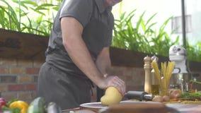 Cuisinier d'homme faisant la pâte pour les pâtes italiennes sur la cuisine Pâte de malaxage de cuisinier de chef sur la table en  banque de vidéos