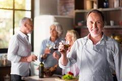 Cuisinier d'une cinquantaine d'années blanc disant un pain grillé regardant l'appareil-photo Photographie stock