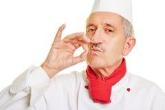 Cuisinier de chef faisant le geste pour le bon goût Image libre de droits