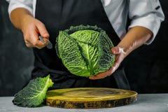 Cuisinier de chef préparant des légumes dans sa cuisine photos libres de droits
