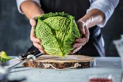 Cuisinier de chef préparant des légumes dans sa cuisine image stock
