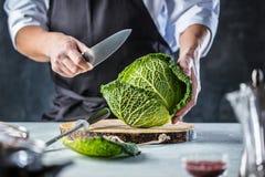 Cuisinier de chef préparant des légumes dans sa cuisine images libres de droits