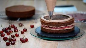 Cuisinier de pâtisserie féminin méconnaissable serrant la crème de chocolat sur le gâteau de couche appétissant dans la cuisine clips vidéos