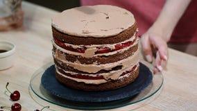 Cuisinier de pâtisserie féminin méconnaissable serrant la crème de chocolat sur le gâteau de couche appétissant dans la cuisine banque de vidéos