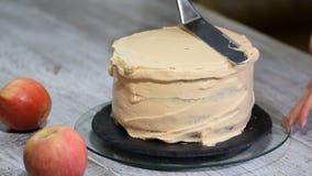 Cuisinier de pâtisserie féminin méconnaissable serrant la crème sur le gâteau de couche appétissant dans la cuisine clips vidéos