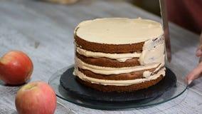 Cuisinier de pâtisserie féminin méconnaissable serrant la crème sur le gâteau de couche appétissant dans la cuisine banque de vidéos