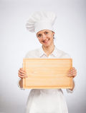Cuisinier de sourire de chef de femme tenant le conseil en bois image libre de droits