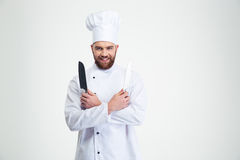 Cuisinier de sourire de chef tenant deux couteaux Images libres de droits