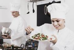 Cuisinier féminin heureux de jeunes tenant le plat Photos libres de droits