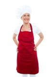 Cuisinier féminin posant avec des mains sur sa taille Photos stock