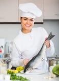 Cuisinier féminin préparant de grands poissons Images libres de droits