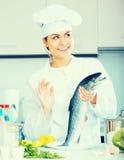 Cuisinier féminin préparant de grands poissons Photographie stock