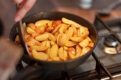 Cuisinier faisant frire les pommes de terre de primeurs Image stock