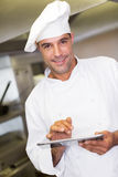 Cuisinier masculin de sourire à l'aide du comprimé numérique dans la cuisine Photo stock