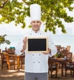 Cuisinier masculin heureux de chef tenant le panneau vide de menu Photos stock