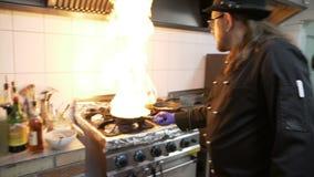 Cuisinier masculin professionnel dans les légumes flamboyants de restaurant dans la casserole utilisant l'huile d'olive banque de vidéos