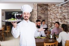 Cuisinier masculin professionnel montrant le restaurant de pays Image libre de droits